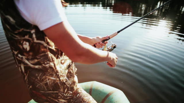 Close-up view of male hands uses the rod with spinning reel. Fisher man spending time in the nature alone video