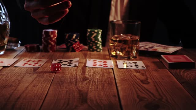 Closeup view of man throwing two dices during casino craps game sitting in a bar in slow motion