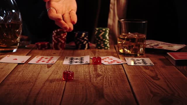 Closeup view of man throwing two dices during casino game sitting in a bar in slow motion