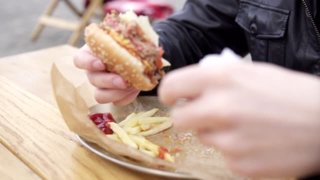 Closeup view of man's hands holding big tasty burger. Man with beard in the street cafe biting tasty big burger with cheese. French fries on the plate. Shot in 4k video