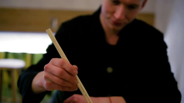Closeup view of man's hands taking chopsticks and starting to eat noodles. Noodles with vegetables. Dinner in japanese restaurant. Delicious baked seafood. video