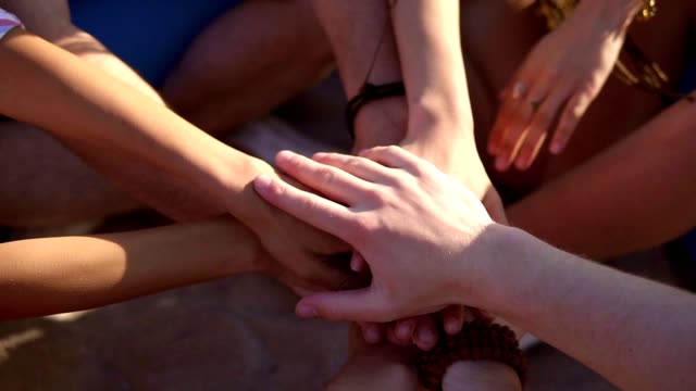 vídeos de stock e filmes b-roll de closeup view of many hands together united in support. teamwork and friendship concept. slowmotion shot - hand