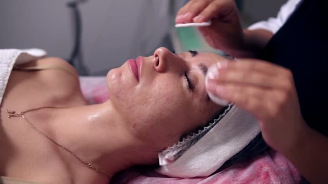 Closeup view of professional cosmetologist is cleaning woman's face using cotton sponge. Young woman is lying on the couch during cosmetic face procedure in spa salon. Face care video