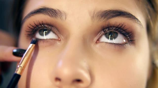 närbild bild av professionell makeup artist händer använder makeup borste för att applicera ögonskuggor. slowmotion skott - makeup artist bildbanksvideor och videomaterial från bakom kulisserna