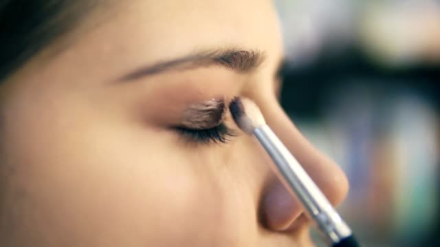 Closeup view of professional makeup artist hands using makeup brush to apply eye shadows. Pro visagiste puts light brown shadows on eyelid of a model. Slowmotion shot video