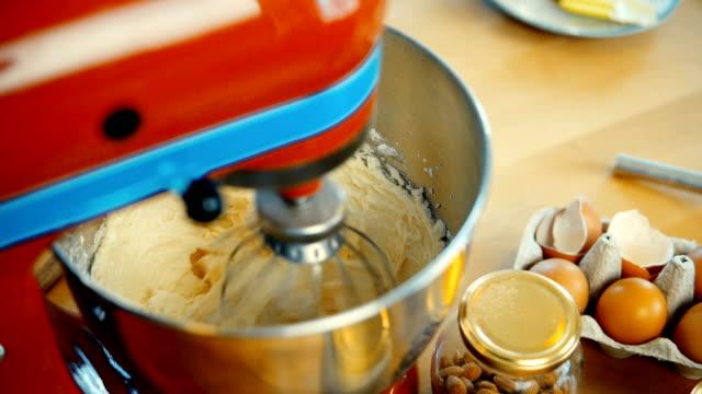 vidéos et rushes de vue rapprochée du rouge mixeur, mélangez la pâte, des ingrédients dans un grand bol. confiseur cuisiner les desserts - batteur électrique
