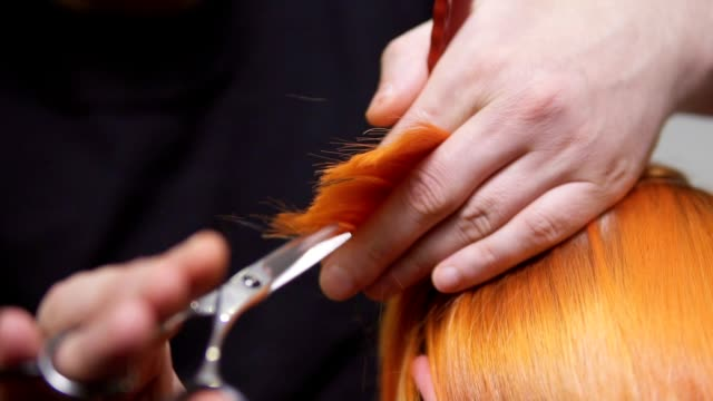 Closeup view of redhead woman's hair being cut by a professional hairdresser in beauty salon. Male hands holding a hair strand and cutting it using scissors and comb. Slowmotion shot Closeup view of redhead woman's hair being cut by a professional hairdresser in beauty salon. Male hands holding a hair strand and cutting it using scissors and comb. Slowmotion shot. hairstyle stock videos & royalty-free footage