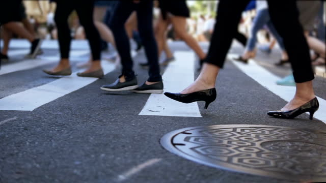 Close-up view of stylish female feet. Businesswoman crossing the road in crowded downtown. Slow motion video