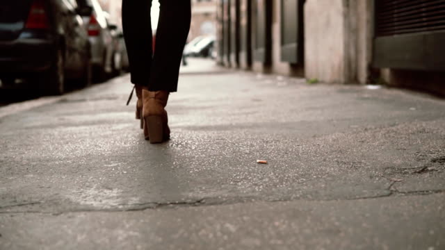 Close-up view of stylish woman walking in little street. Girl wearing shoes on heels goes through the city. Slow motion video