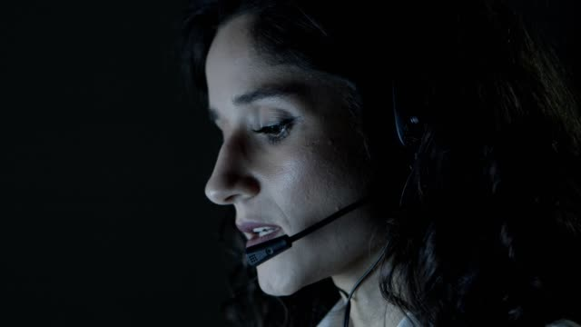 Close-up view of teleworker working at night Close-up view of teleworker working at night. Focused young female call center operator in headset talking and working in dark office. Client support concept call center stock videos & royalty-free footage