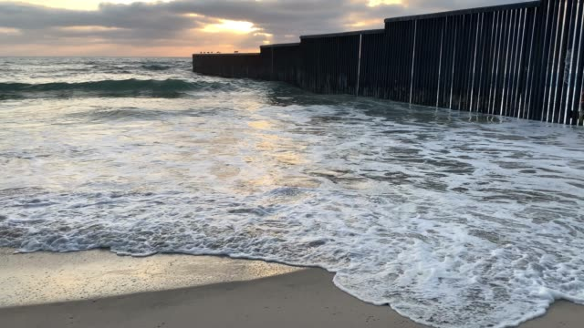 A Close-up View Of The Beach And Waves At Sunset Near The International Border Wall  In Playas Tijuana, Mexico