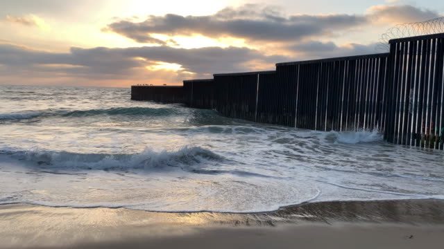 a close-up view of the beach and waves at sunset near the international border wall  in playas tijuana, mexico - ogrodzenie granica filmów i materiałów b-roll