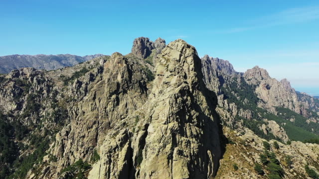 Close-up view of the granite rocks and the Mediterranean Sea of the Col de Bavella in Corsica, France, in summer, by drone.