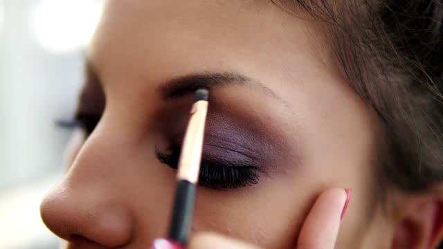 Closeup view of the makeup artist's hands correcting eyebrows using special brush. Slowmotion shot video