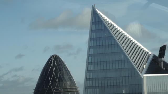 vidéos et rushes de vue en gros plan du haut du bâtiment mary axe également connu sous le nom de gherkin dans le centre de londres, en angleterre. action. gratte-ciel anglais modernes - lame