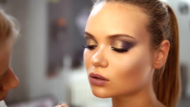 närbild bild av professionell makeup artisten om läppstift använder speciella målningen borste till en kaukasisk modell. läppglans på läpparna. professionell make up - makeup artist bildbanksvideor och videomaterial från bakom kulisserna
