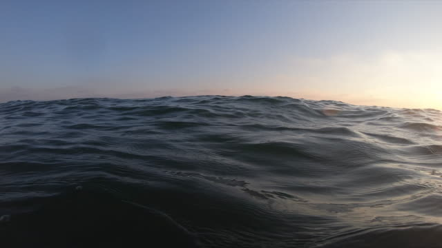 close-up view of wave by sunset slow motion - superficie dell'acqua video stock e b–roll