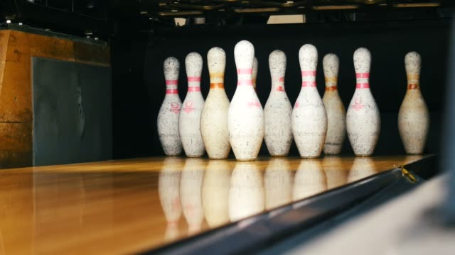 Close-up view of white pins standing in th end of bowling alley lane and rolling bowling ball in a sport club. Media. Funny sport weekends in a bowling