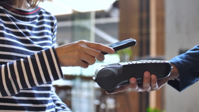Close-up view of Woman paying a NFC transaction with a smartphone in Shop Close-up view of Woman paying a NFC transaction with a smartphone in Shop credit card purchase stock videos & royalty-free footage