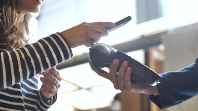 närbild på kvinnan som betalar en nfc-transaktion med en smartphone i butik - lön bildbanksvideor och videomaterial från bakom kulisserna