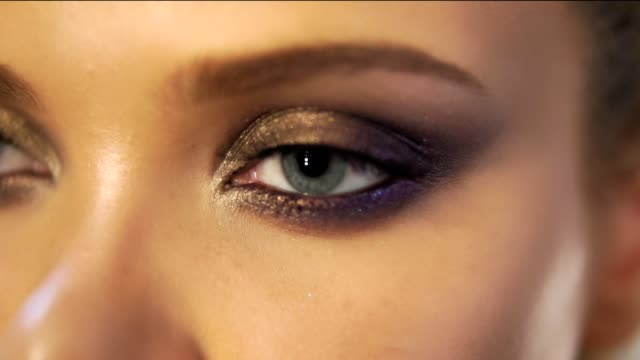 Closeup view of woman's eyes with beautiful golden makeup opening in slowmotion video