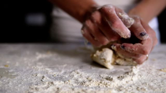 closeup view of woman's hands kneading dough in flour on the table. baker prepares the dough. hands kneadining dough. slow motion shot - impasto video stock e b–roll