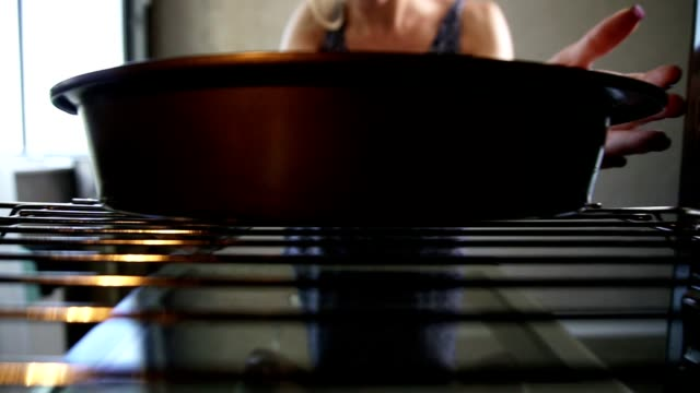 Closeup vista das mãos da mulher tirando uma bandeja de cozimento do forno. Padaria caseira - vídeo