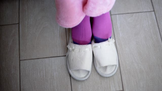 Closeup view of woman's leg putting on the white slippers video