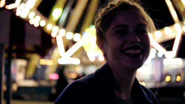 detailansicht der junge schöne glückliche mädchen mit pferdeschwanz lächelnd und blick in die kamera hängen in vergnügungspark mit carusel im hintergrund. slowmotion aufnahme - volksfest stock-videos und b-roll-filmmaterial