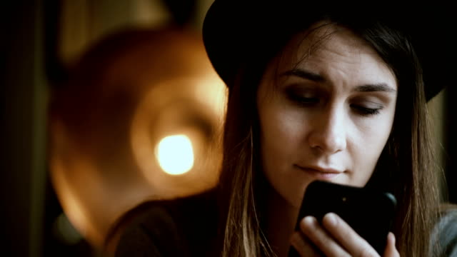 Close-up view of young brunette woman holding the smartphone and typing the message on touchscreen sitting in cafe video