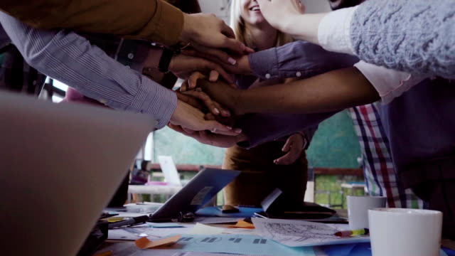 vídeos de stock e filmes b-roll de close-up view of young business team puts palm together two mans fist greeting each other. slow mo - together