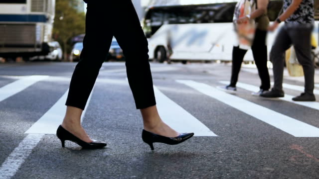 Close-up view of young businesswoman wearing shoes with heels crossing the road in busy downtown. Slow motion