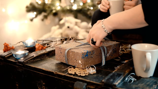 Close-up view of young couple sitting at the table and tie ribbon on present Christmas box in evening video