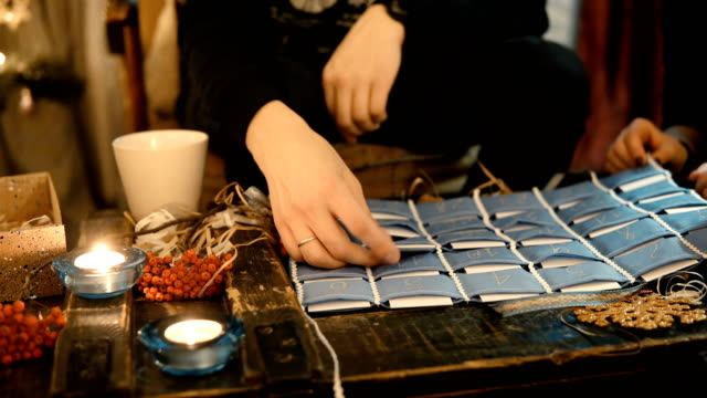 Close-up view of young couple sitting at the table in evening and open the advent calendar together, drinking tea video