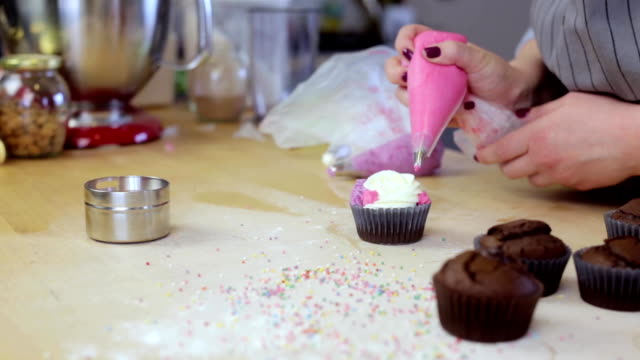 Close-up view of young female hands decorating the chocolate cupcakes with colored cream, using pastry bag for this video