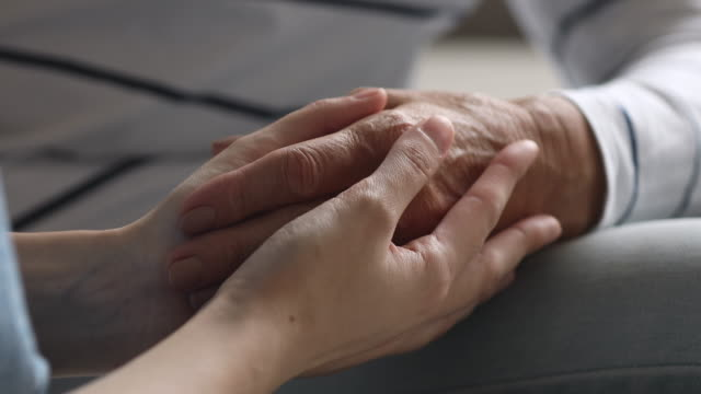 Closeup view of young female hands holding old grandma arm Close up view of young female hands holding old grandma arm as concept of elderly people health care assistance, older grandma support, help in problems, women generations comfort, hope and kindness comfort stock videos & royalty-free footage