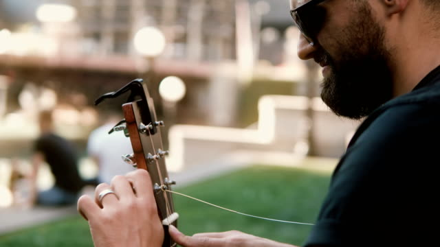 Close-up view of young man in sunglasses restrung, changing string in guitar on the street in sunny summer day video