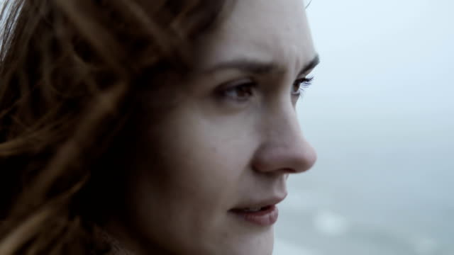Close-up view of young thoughtful woman, looking sad. Pensive attractive female in fog, hair waves on the wind video