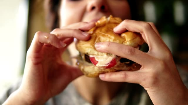 Closeup view of young woman biting big tasty juicy burger in cafe. Slowmotion shot
