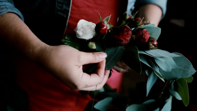 Close-up view of young woman florist making a beautiful flower composition. The decorator makes a wreath video
