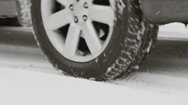 Closeup view on car's wheels wearing Good Year Assurance tires on a drivewai covered by snow.