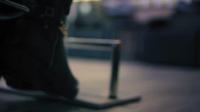 närbild syn på kvinnans svarta stövlar med goldish kedjor stå på ett fotstöd i frisörsalongen - chain studio bildbanksvideor och videomaterial från bakom kulisserna