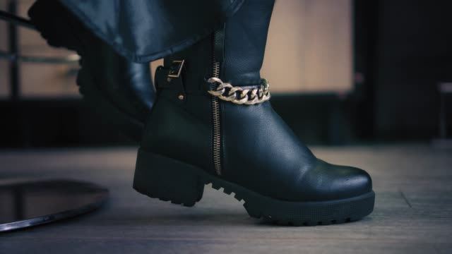 vídeos de stock e filmes b-roll de closeup view on women's black winter boots with goldish chain in shoe store. closeup. - bota