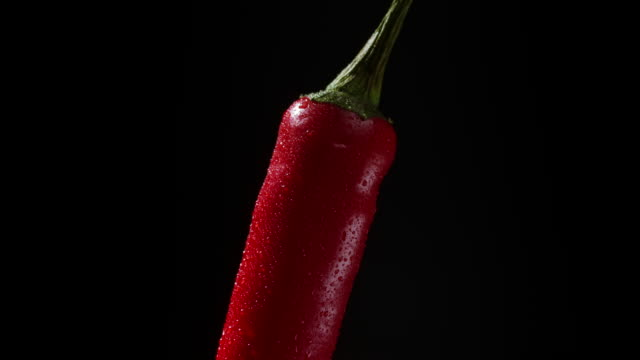 close-up view to rotating red chili pepper with water drops. cayenne isolated on black background. high quality footage. 4k - chilli con carne video stock e b–roll