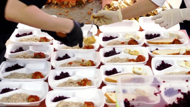 close-up, volunteers pack free hot meals in lunchboxes, for poor people during lock down of covid19. food delivery. charity project, donating aid - szczupły filmów i materiałów b-roll
