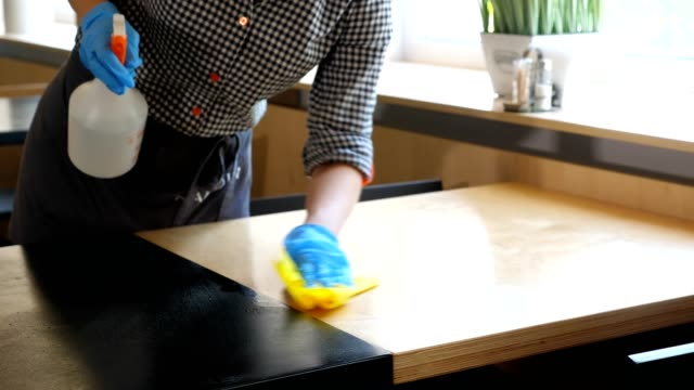 vídeos de stock e filmes b-roll de close-up. waitress, wearing protective gloves, disinfects tables for visitors using antiseptic spray for protect coronavirus. reopening cafeteria or restaurant. safety concept - covid restaurant