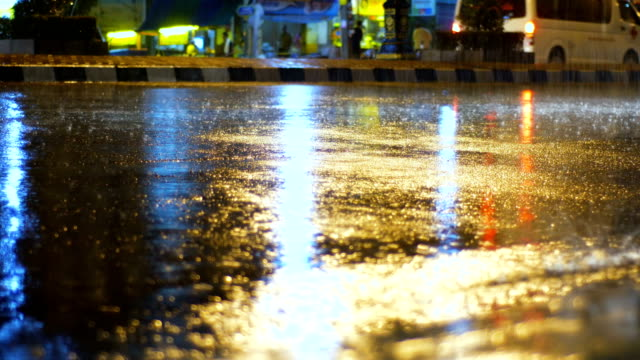 Close-up water while rain on the street with light reflection video