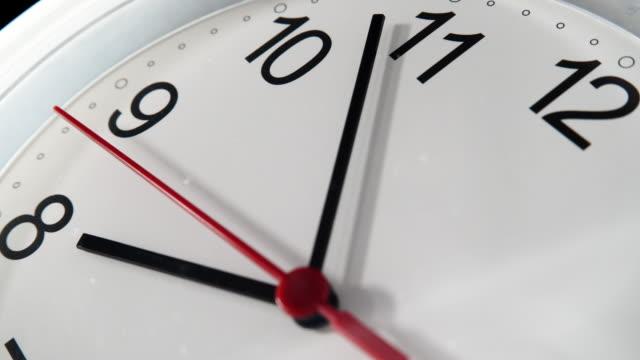 Closeup white clock ticking showing eight, timelapse 4K video