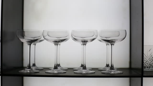 Close-up, wiring from left to right. Many different glasses for alcohol on a rack