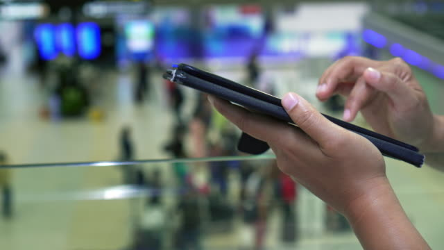 Close-up, woman at the airport is using a mobile phone waiting for boarding